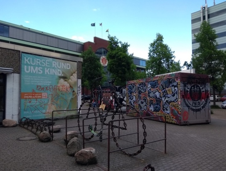 Sculpture of a bicycle in front of a crate decorated with graffiti