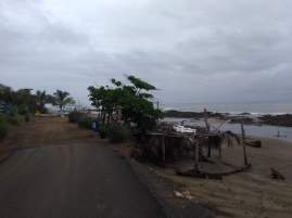 Shacks on beach as the tarmac road ends