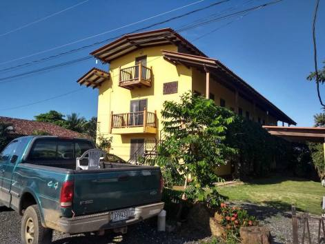 Pedasi Loft. Three storey yellow building with a wooden roof