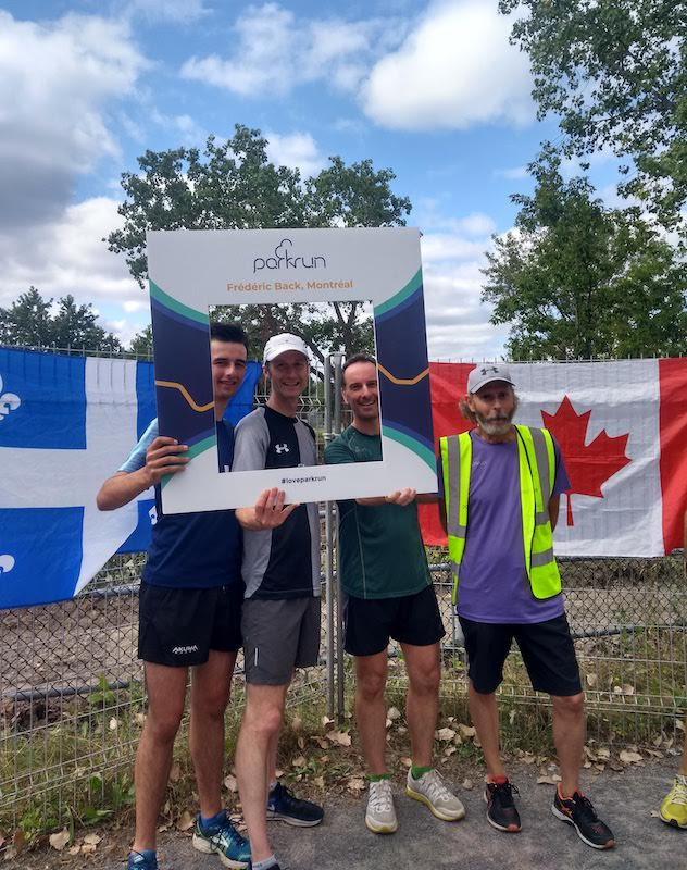 Three runners and the run director posing in front of country flags, post run