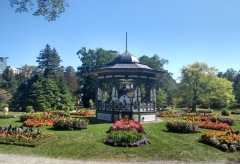 Multiple small flowerbeds with orange and red flowers surround the bandstand