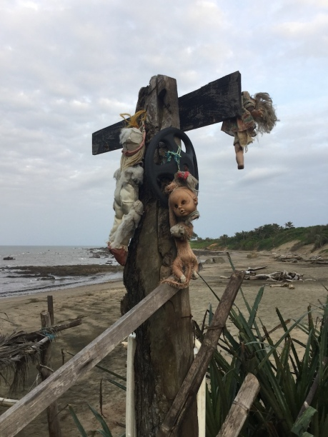 Wooden pole with dolls hung from it, welcoming you to the beach
