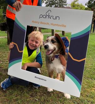 Young boy and dog in hat framed by the run's photo frame