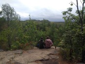 Two girls sit looking out over the forest