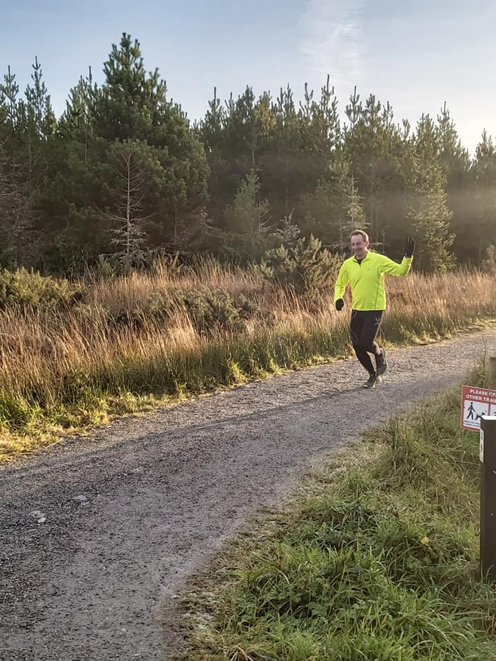 Me, running; long grass and trees behind