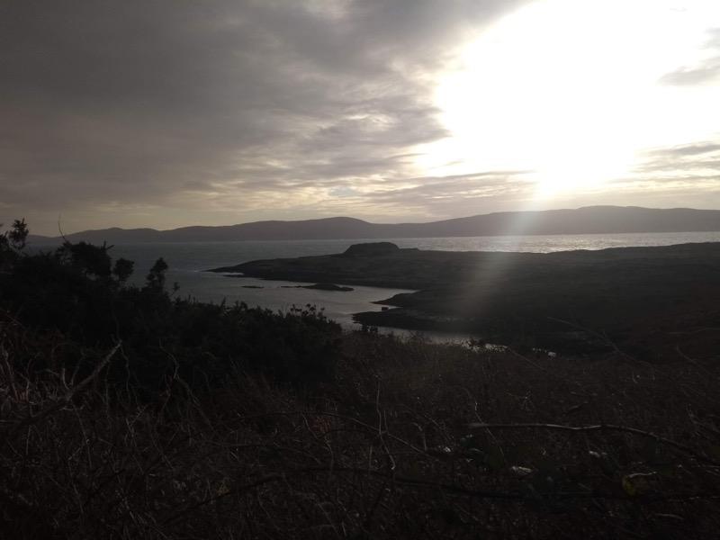 Coastal view, watery sun breaking through clouds