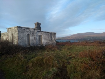 Abandoned house in grass, mainland in sight beneath blue and cloudy sky