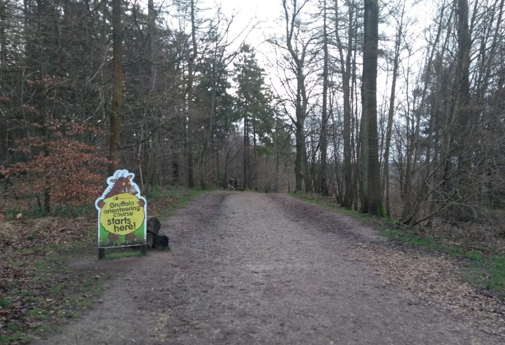 "Woods. Sign on the left says ""Gruffalo orienteering course starts here!"""
