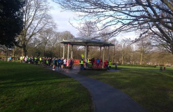 People gathered around the bandstand in the sunshine