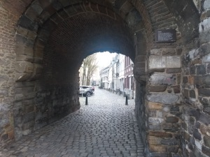 Cobbled street goes under an ancient stone arch