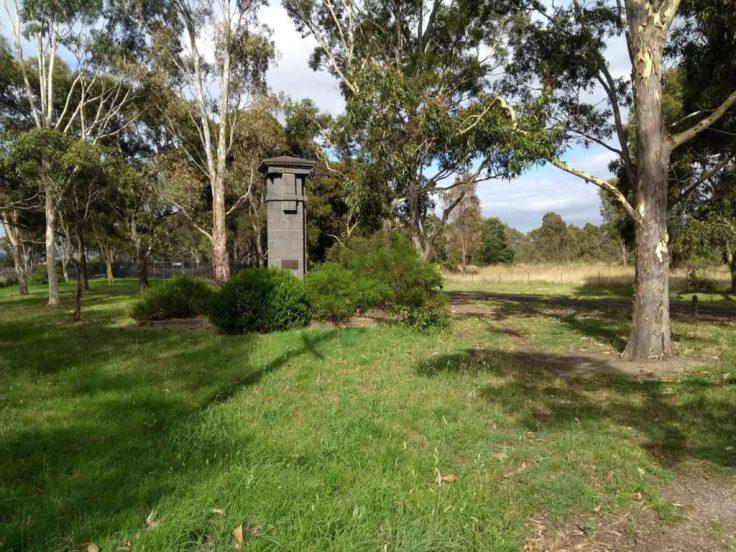 A pillar stands on the grass