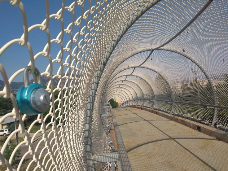 An enclosed footbridge, with padlocks on the wire mesh