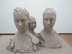 Clay heads with yellow blocks over the left eye