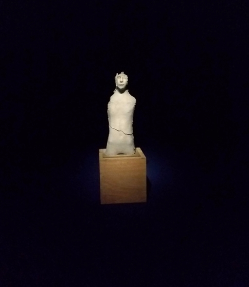 Dark room with a clay figure, spotlit