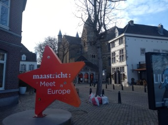 A large star has Maastricht: Meet Europe printed on it, on a cobbled street