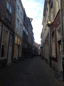 A narrow street, with tall, 3-4 storey houses on either side and a cobbled pavement